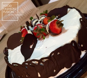 Gorgeous chocolate cake covered in whipped cream surrounded by a chocolate cage. Aren't those strawberries adorable?