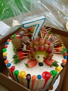 Coloured drip hedgehogs cake with candle in box